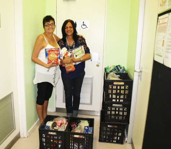 GSCID Social Outreach Manager, Ingrid Frieslaar and Theresa Oakes standing amidst the food donations.